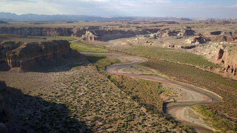 Desert aerial view flying backwards over hilltops viewing Muddy Creek Live Action
