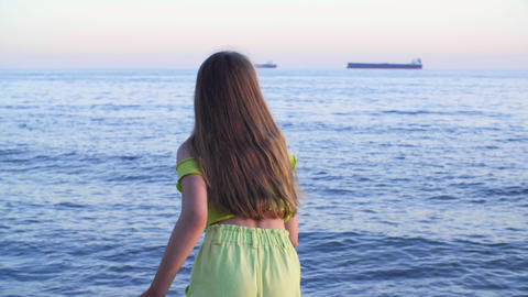 Young girl throwing stones to sea water on cargoship landscape. Tourist girl Live Action