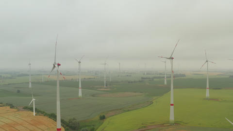 AERIAL: Multiple Wind Turbines on rich yellow agriculture field in Fog rotating Live Action
