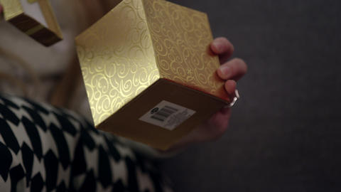 Close up view of woman handing gift box to another person Live Action