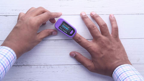 Man finger with pulse oximeter to measure oxygen saturation Live Action