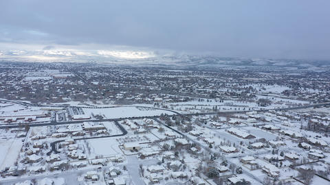 Aerial view flying over suburbs viewing traffic in snow covered landscape Live Action