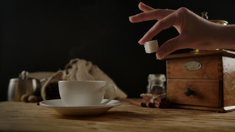 Adding sugar cube by fixed elegant hand in white coffee cup. Light splash Live Action