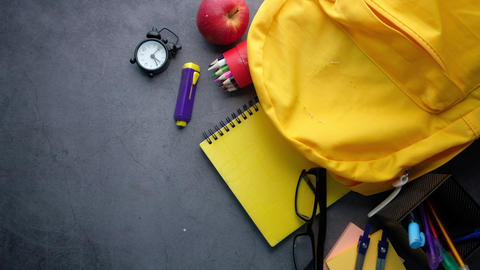 Back to school concept yellow backpack and school suppliers on black background Live Action