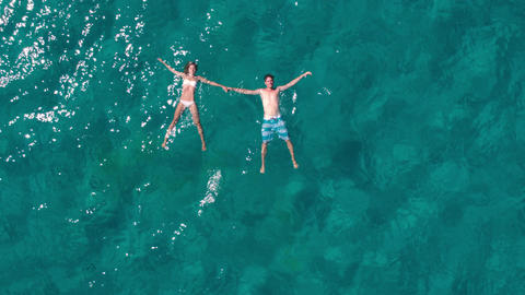 Aerial - Happy young couple floating in crystal clear water Live Action