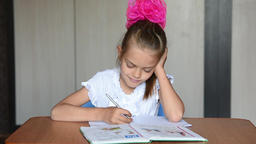 Seven-year girl schoolgirl doing homework sitting at table at home Footage