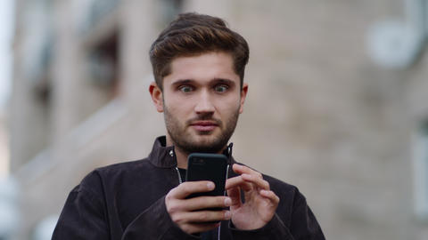 Happy man using phone outside. Excited guy scrolling device outdoors Live Action