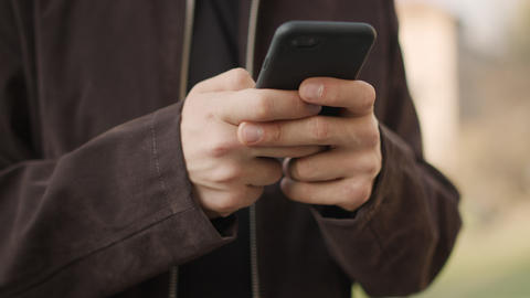 Male hands using mobile phone outdoors. Unknown guy texting phone outside Live Action
