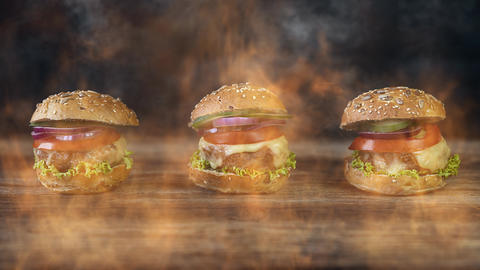 Hamburgers served on a rustic wooden surface surrounded by smoke and burning fire Videos animados