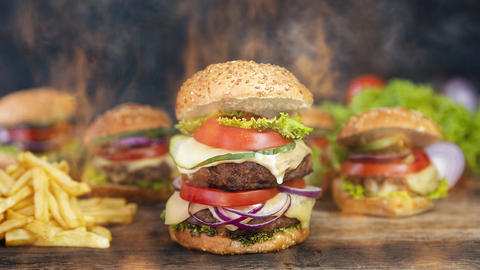 Hamburger served on a rustic wooden surface surrounded by smoke and burning fire Videos animados