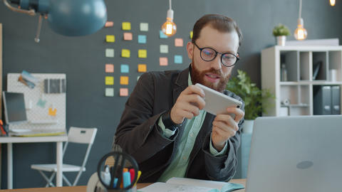 Joyful guy enjoying mobile video game playing alone in creative office relaxing Live Action