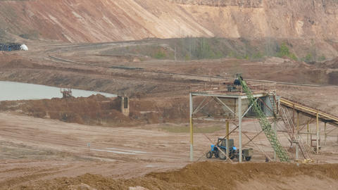 Tractor and trucks works in the sand ballast quarry on the cloudy summer day ライブ動画