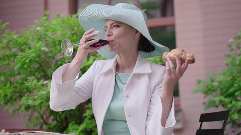 Attractive woman drinking wine, smelling croissant and smiling at camera Live Action