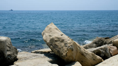 Close-up of a stone beach on a clear day. Rocks and pebbles on the beach, flooded with sea spray and Live Action