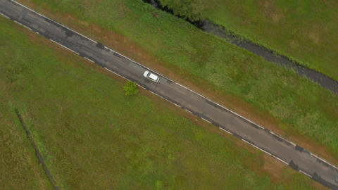 Top Down Overhead Aerial View of Electric Vehicle driving trough Nature on small Live Action
