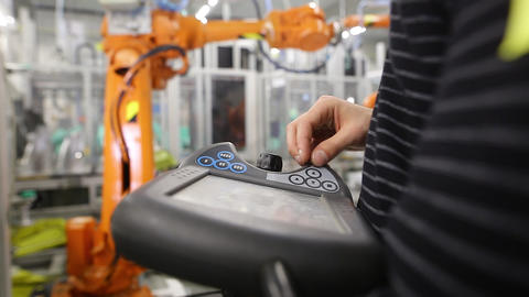 Man programming robot in automotive industrial, professional programmer Live Action