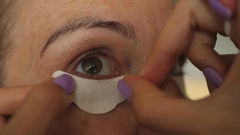 putting apply applying eye protection paper papers under eye Live Action