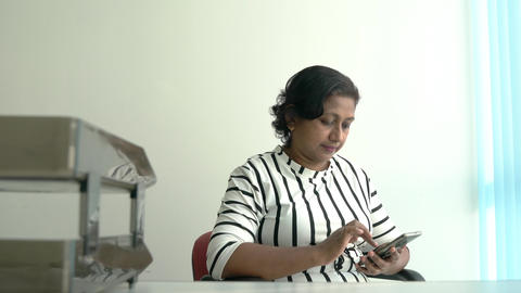 Attractive Indian businesswoman sitting inside her office using her cellphone Live Action