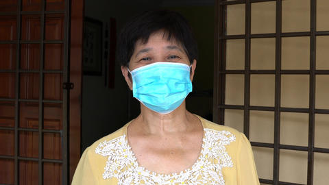 Elderly Chinese woman, wearing medical face mask. Standing outside her house Live Action