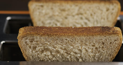 Close-up of two slices of bread in a toaster. Selective focus from the front Live Action