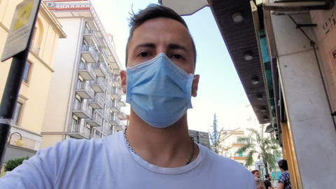 Young man walking aroung city with coronavirus protective mask,covid19 disease Live Action