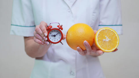 Nutritionist Doctor Healthy Lifestyle Concept - Holding Orange Fruit and Alarm Clock 4 Live Action