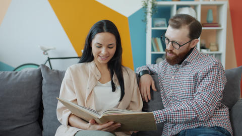 Man and woman reading book together talking and enjoying leisure time at home Live Action
