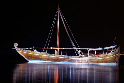 Traditional wooden boat(dhow) in Arabic gulf at nigh with reflection in water in Doha, Qatar Fotografía