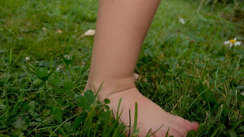 children's bare feet stomp across the grass. Fun outdoors Live Action