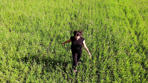 woman running and jumping in a green field outdoors, happiness concept, freedom Live Action