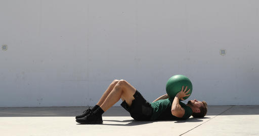 Strength training fit man cross training throwing medicine ball in the air for Live Action