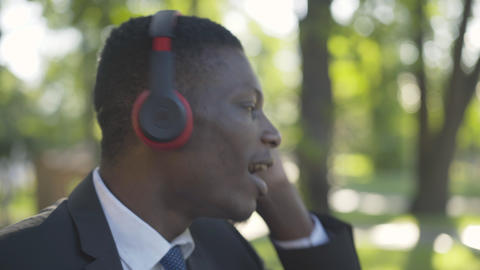 Close-up face of cheerful African American man enjoying music in headphones Live Action