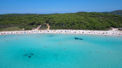 Aerial - Flying above bay of clear, turquoise water and over white sandy beach Footage
