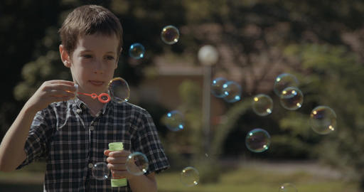 young boy blowing soap bubbles outdoors Footage