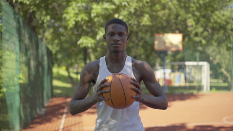 Portrait of confident African American sportsman posing with ball on basketball Live Action