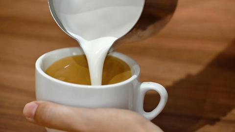 Close-up view of a barista demonstrating the art of pouring and preparing a cup Live Action