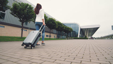 Woman walking with luggage. The girl goes on a journey and walks to the airport Live Action