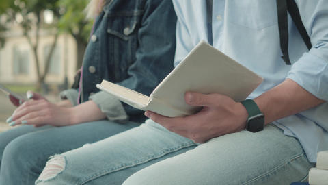 Close-up of unrecognizable young man sitting with book outdoors and young girl Live Action