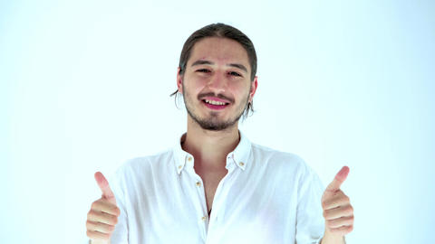 Portrait of handsome young man looking approvingly at camera and gesturing double thumbs up. Studio GIF
