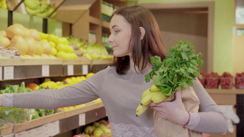 Positive young woman smelling bunch of parsley in supermarket. Portrait of Live Action