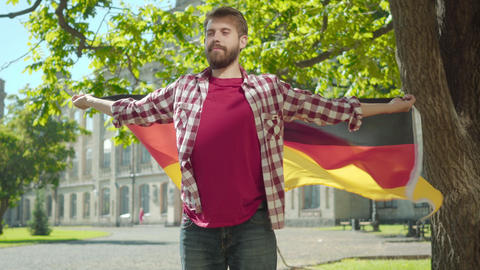 Portrait of confident positive bearded man standing with hands spread on sunny Live Action