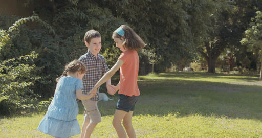 Three kids running and playing together on the lawn Footage