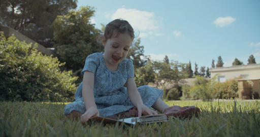 Little girl reading a children's book outdoors Footage