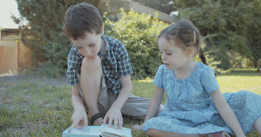 Little girl reading a children's book outdoors with her brother Footage