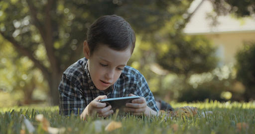 young boy sitting outdoors playing with a smartphone Live Action