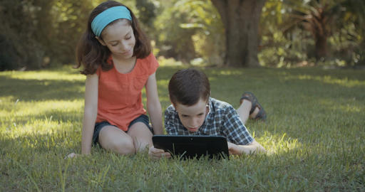 Young girl and boy playing with a tablet computer outdoors on the lawn Footage