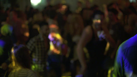 DJ playing music and people dancing in a dance party Live Action