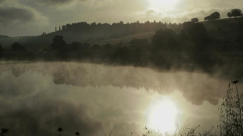 Fog rising from a lake at sunrise 画像