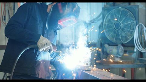 Welder welding metal parts in a metal workshop Live Action