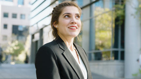 Young business woman standing on the street smiling to the camera GIF